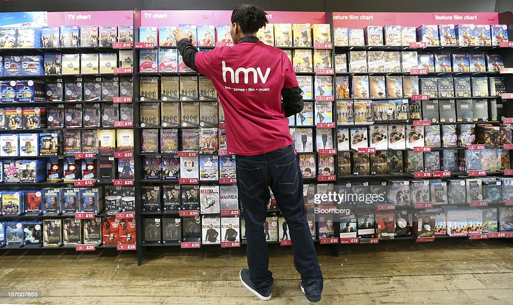 An employee arranges DVDs on a display inside a HMV pop-up store, in this arranged photograph in London, U.K., on Tuesday, Nov. 27, 2012. Fashion chain Hobbs is among those that have opened pop-up stores for the first time this year, while CD and DVD retailer HMV Group Plc is adding more than usual for the holiday in an effort to win business. Photographer: Chris Ratcliffe/Bloomberg via Getty Images