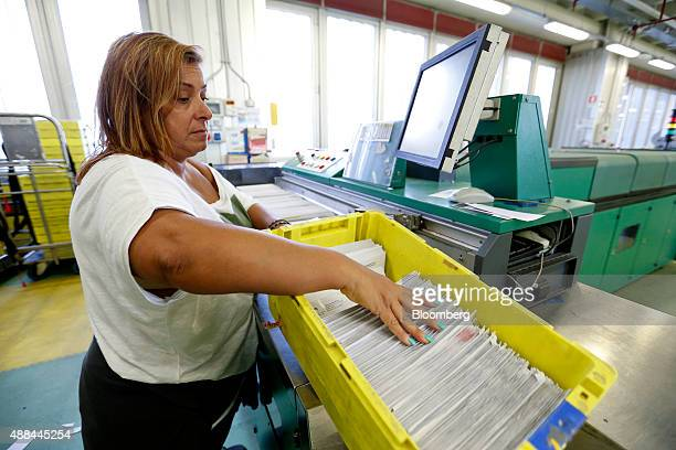 An employee arranges envelopes inside a Poste Italiane SpA postal sorting office in Fiumicino near Rome Italy on Tuesday Sept 15 2015 Italy is...
