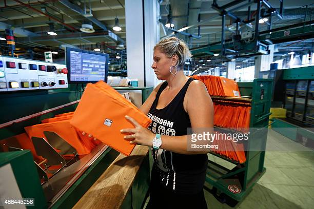 An employee arranges envelopes onto a machine inside a Poste Italiane SpA postal sorting office in Fiumicino near Rome Italy on Tuesday Sept 15 2015...