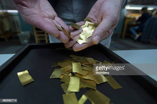 An employee arranges flakes of gold in the workshop for the Zolotos SA luxury jewelry store in Athens Greece on Monday July 13 2015 Greece has been...