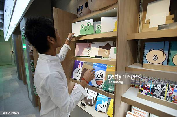 An employee arranges Line Corp character merchandise on display at the Line Friends Store in Tokyo Japan on Thursday Dec 10 2014 Line which makes...