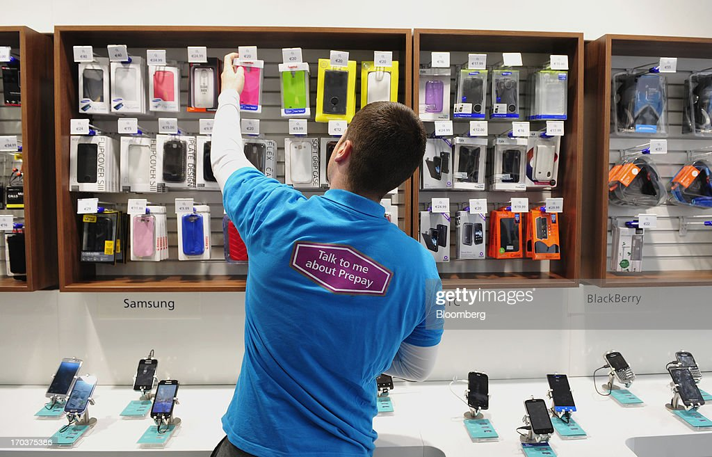 An employee arranges mobile phone covers inside an O2 Mobile Phone Store, part of Telefonica SA, on Grafton Street in Dublin, Ireland, on Wednesday, June 12, 2013. Telefonica SA, Europe's most indebted telephone company, is seeking initial bids for its Irish unit within the month, two people with knowledge of the matter said. Photographer: Aidan Crawley/Bloomberg via Getty Images