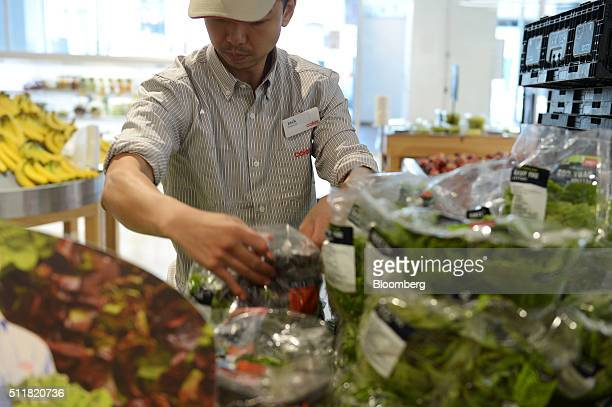 An employee arranges packaged lettuce in the produce section of a Coles supermarket operated by Wesfarmers Ltd in Melbourne Australia on Tuesday Feb...