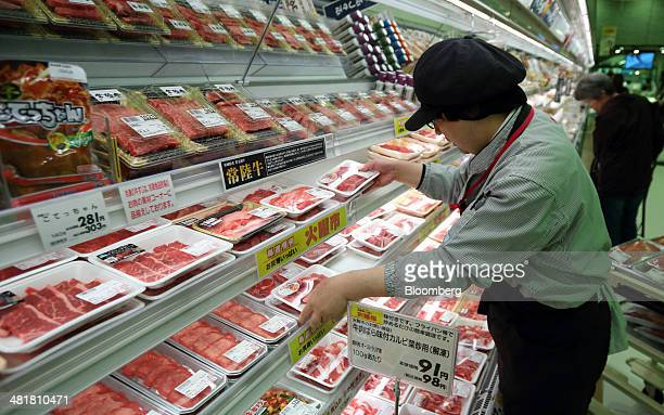An employee arranges packs of beef imported from Australia at an Aeon Co supermarket in Chiba Japan on Tuesday April 1 2014 Japan's economy will...