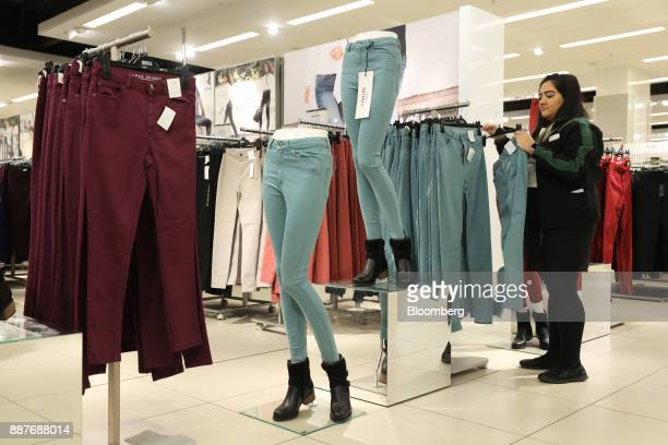 An employee arranges pairs of skinny jeans hanging on a rail inside a branch of Marks Spencer Group Plc in London UK on Tuesday Dec 5 2017 Brexit...