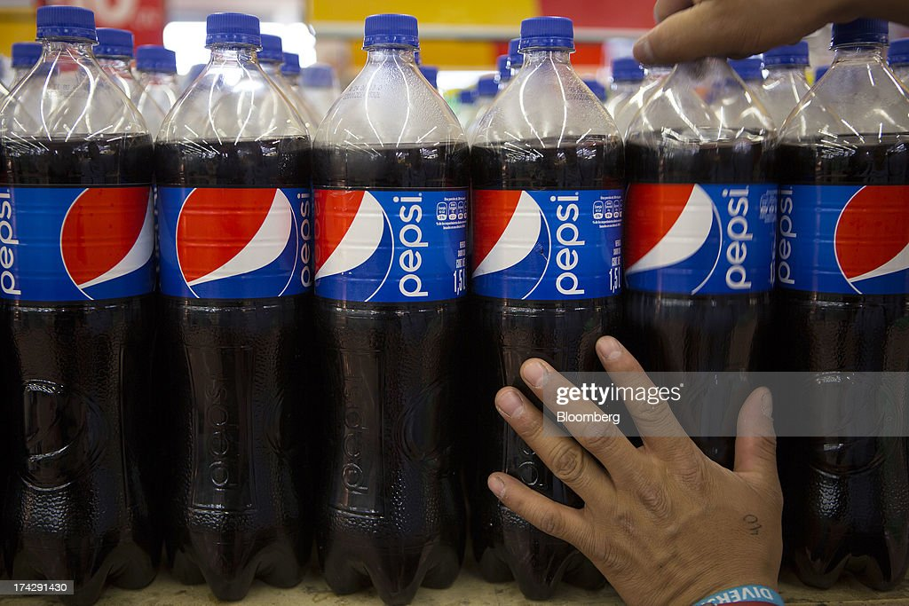 An employee arranges PepsiCo Inc. soft drink bottles on display at a store in Mexico City, Mexico, on Monday, July 22, 2013. PepsiCo Inc. is expected to release earnings data on July 24. Photographer: Susana Gonzalez/Bloomberg via Getty Images