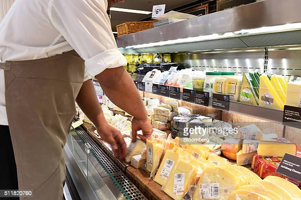 An employee arranges products in the cheese section of a Coles supermarket operated by Wesfarmers Ltd in Melbourne Australia on Tuesday Feb 23 2016...