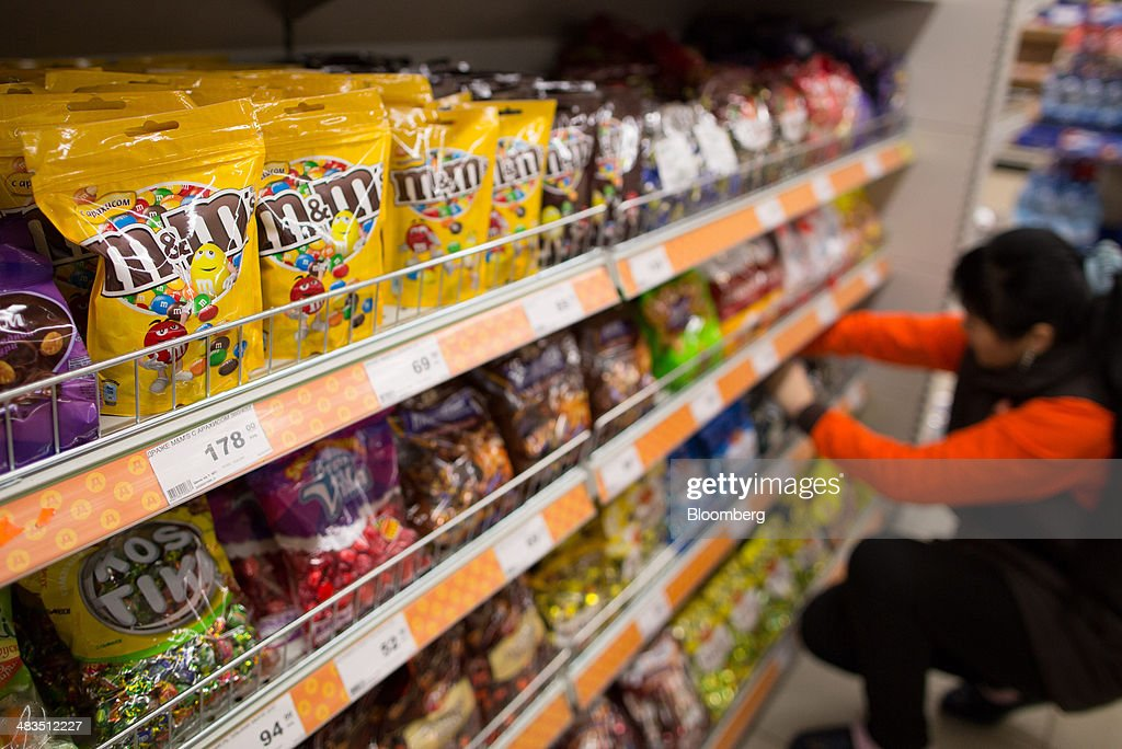 An employee arranges products on a display of confectionary which includes bags of M&M's candy, produced by U.S. manufacturer Mars Inc., inside a Dixy supermarket operated by OAO Dixy Group in Moscow, Russia, on Tuesday, April 8, 2014. Suppliers suffering from ruble depreciation this quarter are urging retailers to increase prices. Photographer: Andrey Rudakov/Bloomberg via Getty Images