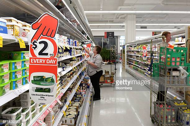 An employee arranges products on shelves in the dairy aisle of a Coles supermarket operated by Wesfarmers Ltd in Melbourne Australia on Tuesday Feb...