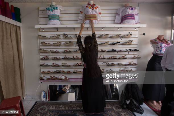 An employee arranges Puruhastyle handembroidered blouses at a store in Riobamba Ecuador on July 1 2017 The thriving indigenous fashion industry in...