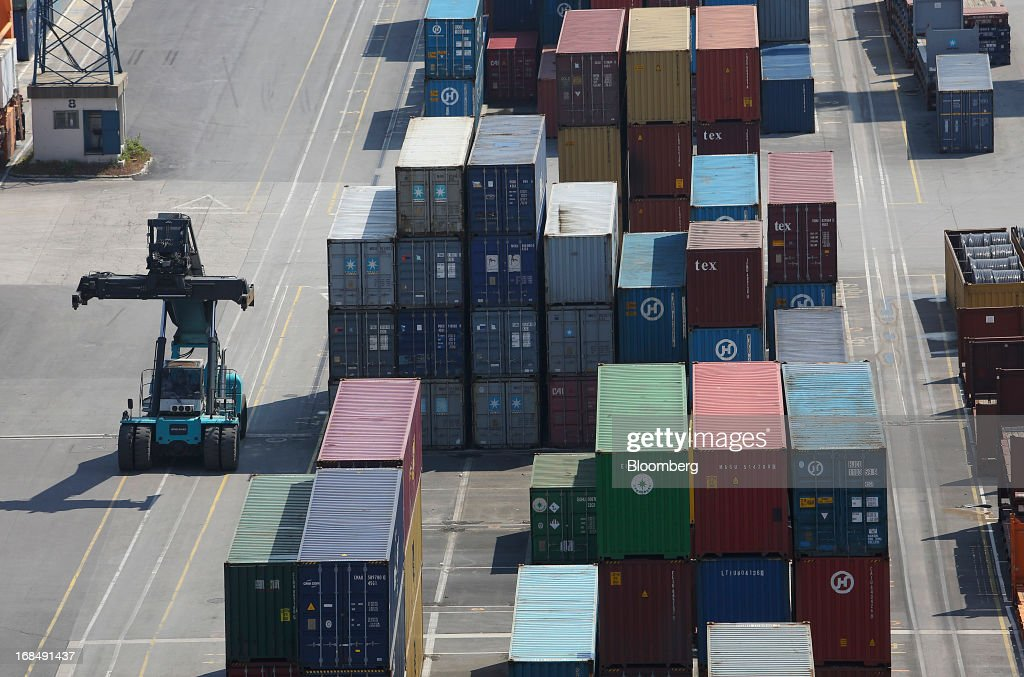 An employee arranges shipping containers on the dockside at the port of Koper, operated by Luka Koper d.d., in Koper, Slovenia, on Thursday, May 9, 2013. The former Yugoslav nation, mired in its second recession since 2009, will contract this year and next, according to a May 3 report by the European Commission. Photographer: Chris Ratcliffe/Bloomberg via Getty Images