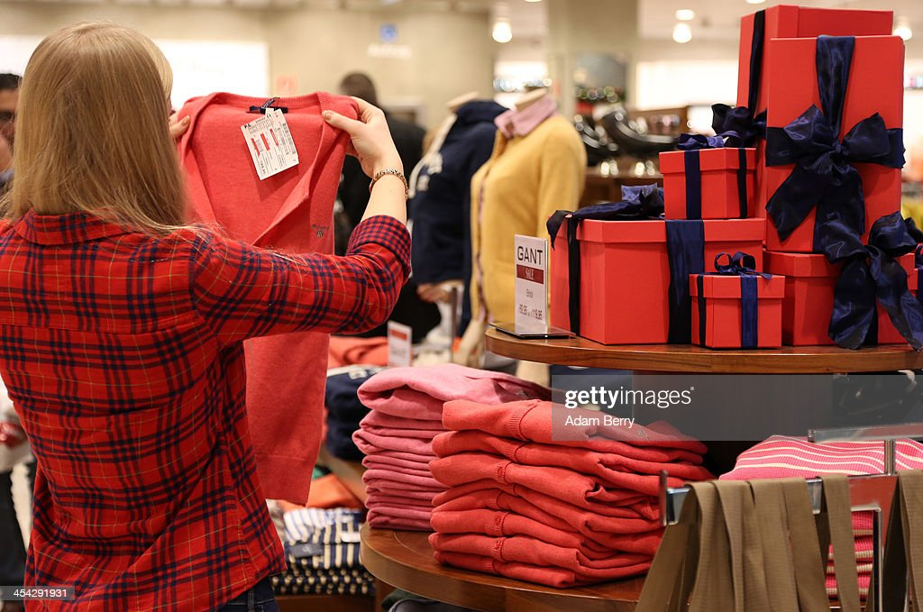 An employee arranges sweaters in a department store on December 8 2013 in Berlin Germany Germans spend an average of 400 euros on Christmas presents...