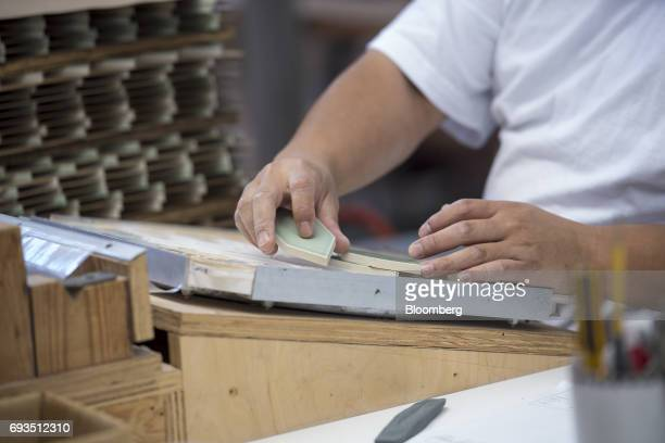 An employee arranges tile pieces into design patterns to be packaged at the Heath Ceramics Ltd production facility in San Francisco California US on...