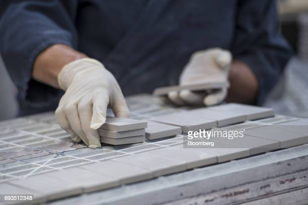 An employee arranges tile squares to be glazed at the Heath Ceramics Ltd production facility in San Francisco California US on Friday June 2 2017 The...