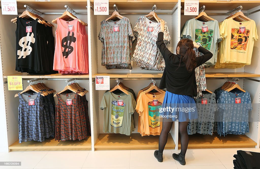 An employee arranges t-shirts displayed at Fast Retailing Co.'s Uniqlo store in the Ginza district of Tokyo, Japan, on Wednesday, April 10, 2013. Fast Retailing, Asia's largest apparel retailer, is scheduled to announce earnings tomorrow. Photographer: Yuriko Nakao/Bloomberg via Getty Images
