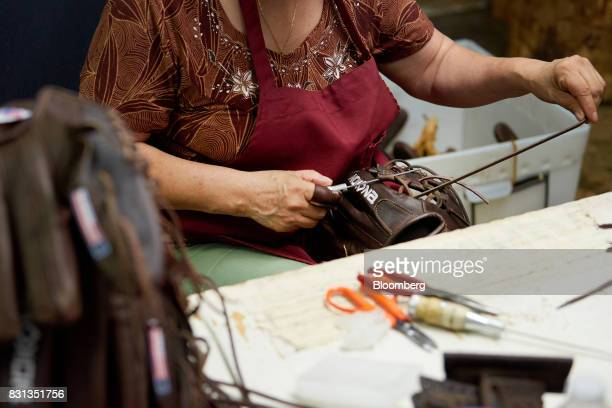 An employee assembles a ball glove at the Nokona manufacturing facility in Nocona Texas US on Thursday July 27 2017 Since the Great Depression Nokona...