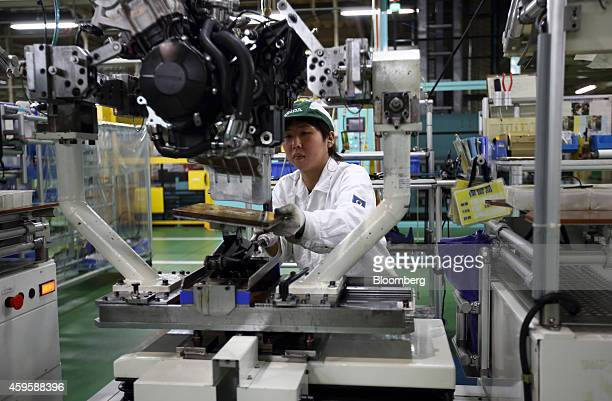 An employee assembles a Honda Motor Co motorcycle engine on the production line during a tour of the company's Kumamoto factory in Ozu Kumamoto...