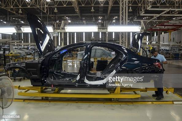 An employee assembles a part of a MercedesBenz EClass vehicle on the production line of a MercedesBenz factory in Bogor Indonesia on January 24 2017...