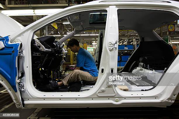 An employee assembles a Ssangyong Motor Co Korando C sportutility vehicle on the production line at the company's factory in Pyeongtaek South Korea...