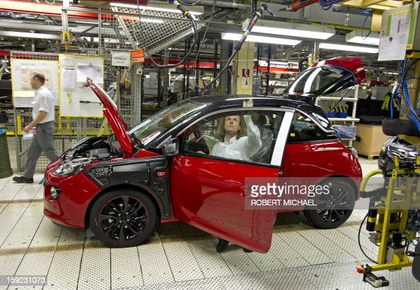An employee assembles an Opel Adam car at the Opel plant in Eisenach eastern Germany on January 10 2013 The new Opel model will be produced as of...