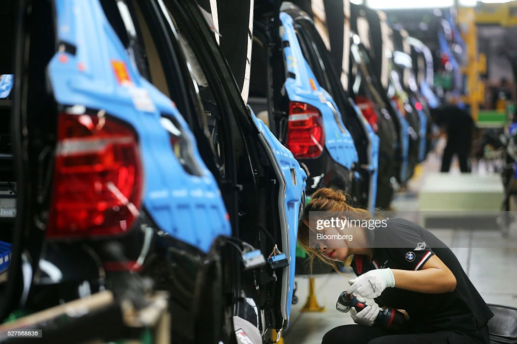 An employee assembles the body of a BMW AG X3 vehicle at a BMW manufacturing plant in Pluak Daeng, Rayong Province, Thailand, on Tuesday, May 3, 2016. BMW's profit declined 2.5 percent in the first quarter on investment in new technologies like self-driving cars to defend its status as the world's biggest maker of luxury vehicles. Photographer: Dario Pignatelli/Bloomberg via Getty Images