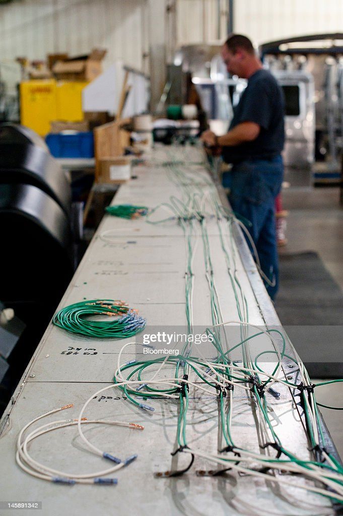 An employee assembles wiring harnesses for trailers on the assembly line at the Airstream Inc. manufacturing facility in Jackson Center, Ohio, U.S., on Wednesday, June 6, 2012. The U.S. Federal Reserve is scheduled to release industrial production data on June 15. Photographer: Ty Wright/Bloomberg via Getty Images