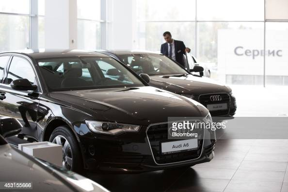 An employee assists a customer as he inspects the interior of an Audi A4 vehicle on display inside an Audi AG showroom in Moscow Russia on Saturday...