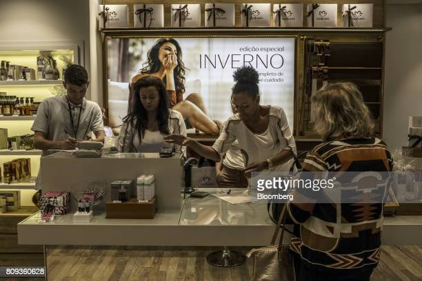 An employee assists a customer at a checkout counter in a Natura Cosmeticos SA store inside the Santos Dumont Airport in Rio de Janeiro Brazil on...