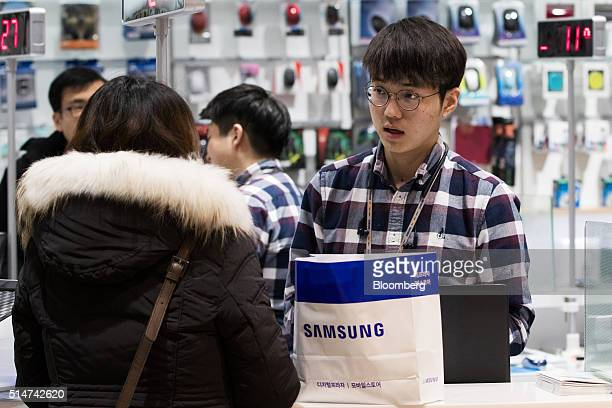 An employee assists a customer at a Samsung Electronics Co D'light flagship store in Seoul South Korea on Friday March 11 2016 Samsung's latest...
