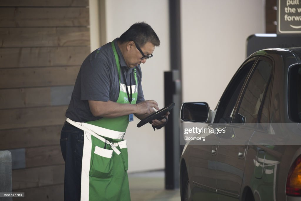 An employee assists a customer at an AmazonFresh Pickup location in Seattle, Washington, U.S., on Friday, May 26, 2017. Amazon.com Inc. opened two grocery pickup kiosks in Seattle, part of its latest effort to enter the $800 billion grocery market and compete with 'click and collect' shopping options from big box competitors like Wal-Mart Stores Inc.