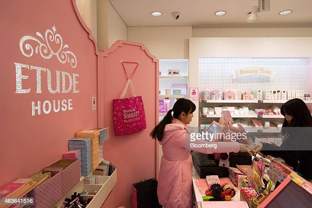 An employee assists a customer at the checkout counter of an Amorepacific Corp Etude House store in the Myeongdong shopping district in Seoul South...
