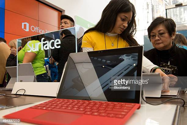 An employee assists a customer with a Surface Pro tablet computer during the opening of the first Microsoft Corp store in New York US on Monday Oct...