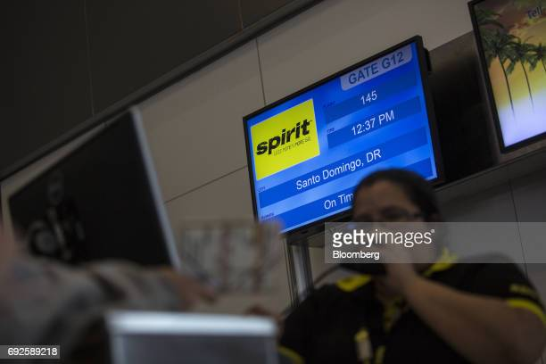 An employee assists a traveler at the Spirit Airlines Inc ticket counter at Fort Lauderdale International Airport in Fort Lauderdale Florida US on...