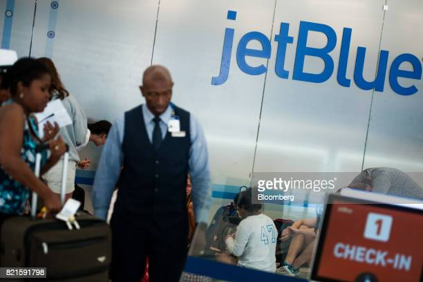 An employee assists a traveler with baggage at the JetBlue Airways Corp Terminal 5 inside John F Kennedy International Airport in New York US on...