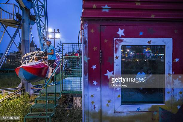 An employee assists a visitor on a carnival ride at the National Amusement Park known as the Children's Park in Ulaanbaatar Mongolia on Wednesday...