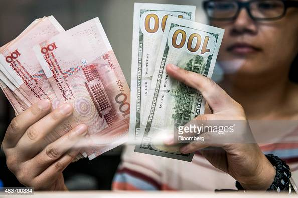 An employee at a currency exchange store counts Chinese onehundred yuan and US onehundred dollar banknotes in Hong Kong China on Wednesday Aug 12...