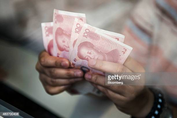 An employee at a currency exchange store counts Chinese onehundred yuan banknotes in Hong Kong China on Wednesday Aug 12 2015 The yuan sank for a...
