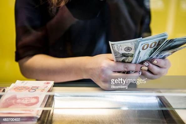 An employee at a currency exchange store counts US onehundred dollar banknotes next to a pile of Chinese onehundred yuan bills in Hong Kong China on...
