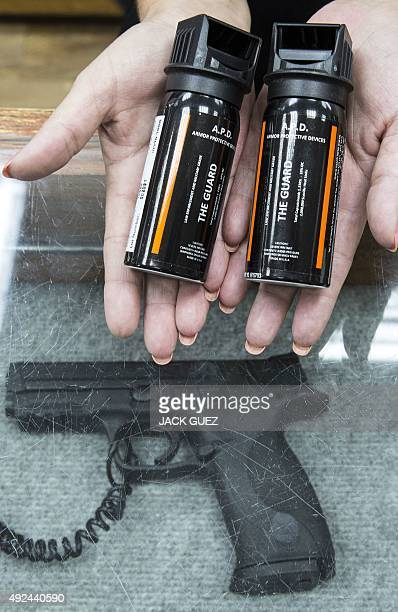 An employee at a gunsmiths and indoor shooting range in the Israeli coastal city of Tel Aviv shows pepper spray to a customer on October 13 2015 The...