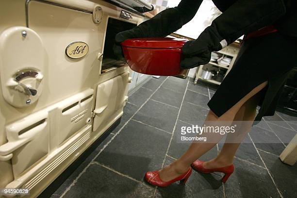 An employee at an AGA store in Knightsbridge London UK places a casserole dish in the oven of an AGA stove Friday July 6 2007 Aga service Group Plc...