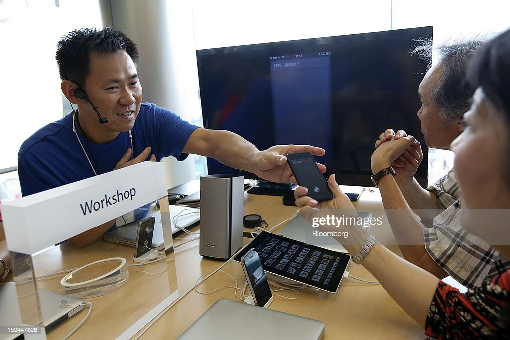 An employee at Apple Inc.'s store demonstrates using an iPhone 5 in Hong Kong, China, on Friday, Sept. 21, 2012. Apple is poised for a record iPhone 5 debut and may not be able to keep up with demand as customers line up from Sydney to New York to pick up the latest model of its top-selling product. The device hits stores in eight countries today at 8 a.m. local time, giving customers in Australia the first chance to buy the device. Photographer: Daniel J. Groshong/Bloomberg via Getty Images