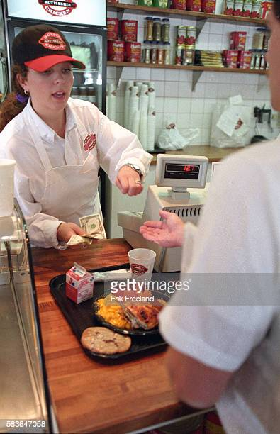 An employee at Boston Chicken gives a customer change after a purchase