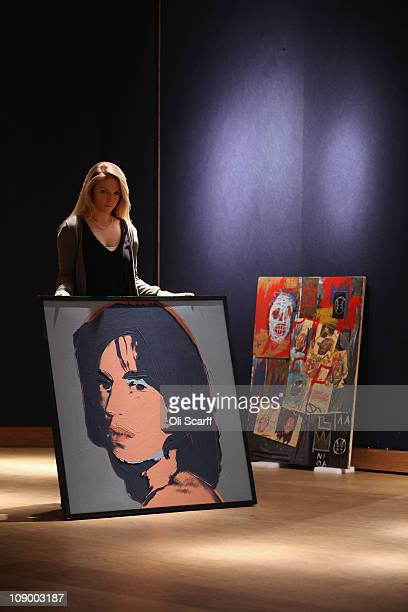 An employee at Christie's auction house holds a painting by Andy Warhol entitled 'Mick Jagger' in front of 'Untitled' by JeanMichel Basquiat on...