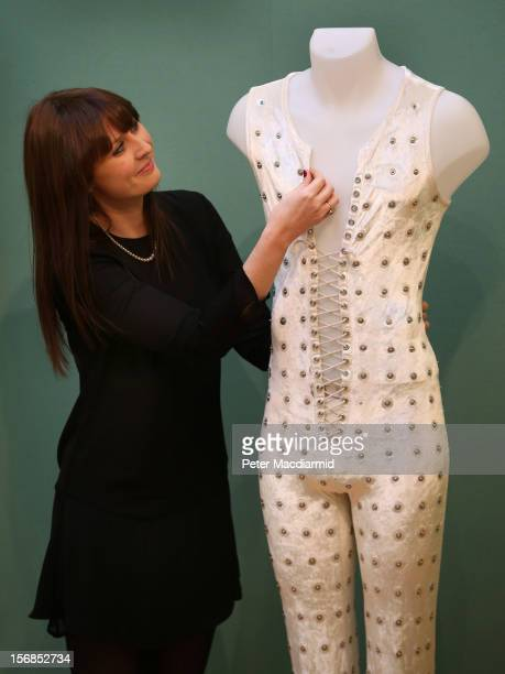 An employee at Christie's looks at a laceup sleeveless jumpsuit designed by Ossie Clark for Mick Jagger for the Rolling Stones' US Tour in 1972 on...