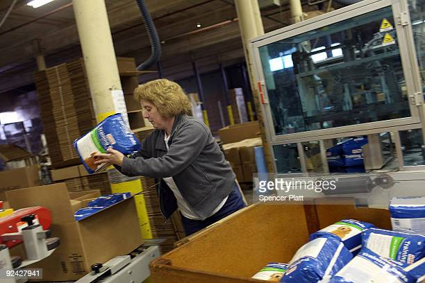 An employee at the American Disposables Inc factory stacks bags of diaper pads October 28 2009 in Ware Massachusetts The factory which has been...