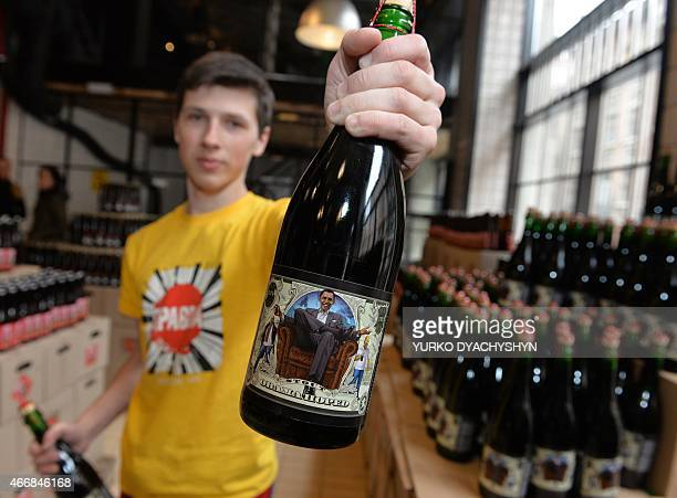 An employee at the Beer Theater a restaurant in the western Ukrainian city of Lviv shows on March 19 2015 a bottle of Obama Hoped stout brewed at the...