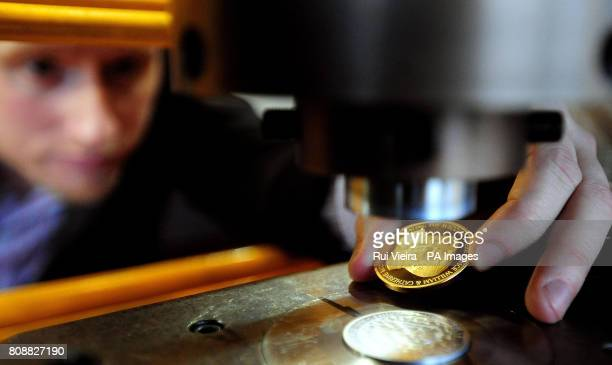 An employee at the Birmingham Mint removes a commemorative coin from a press during the launch of the coin by Birmingham Mint to celebrate the future...