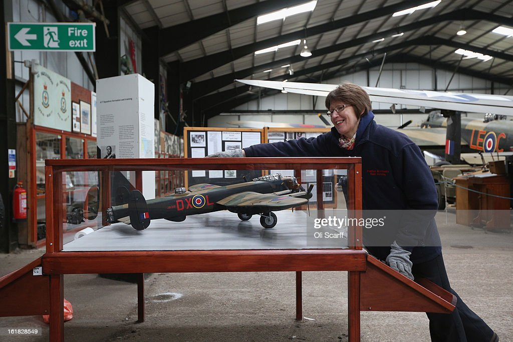 An employee at the Lincolnshire Aviation Heritage Centre cleans a display case in the hangar of the Lancaster bomber 'Just Jane', which is being restored with the aim of getting it airworthy, on February 14, 2013 in East Kirkby, England. The plane, which last flew in 1971, would become one of only three airworthy Lancaster bombers in the world. Brothers Fred and Harold Panton, owners of the Lincolnshire Aviation Heritage Centre, are restoring the plane in memory of their sibling, Christopher Panton, who died aged 19 when his Lancaster was shot down in 1944.