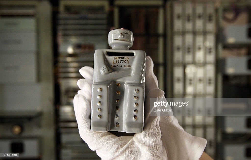 An employee at the Science Museum holds an Ernie money box in front of 'Ernie' the first Premium Bonds generator before it goes on display on June 19...
