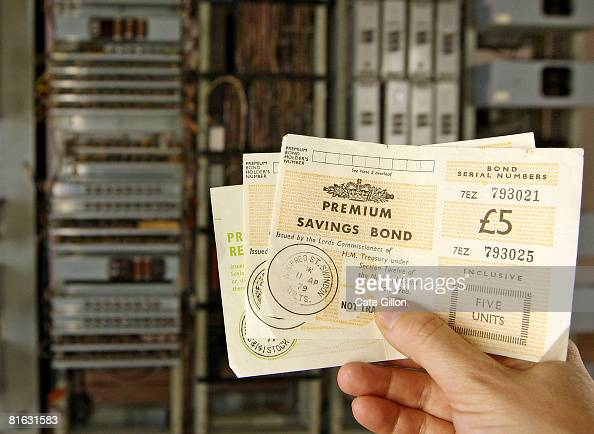 An employee at the Science Museum holds Premium Bonds in front of 'Ernie' the first Premium Bonds generator before it goes on display on June 19 2008...